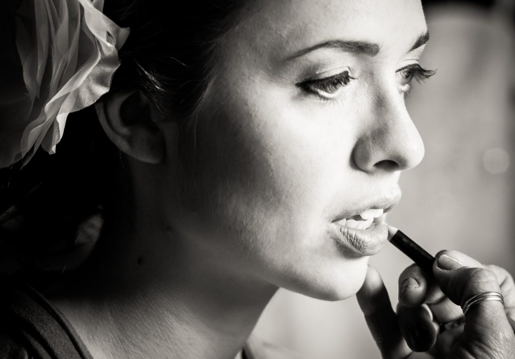 Black and white photo of lipstick being applied to bride