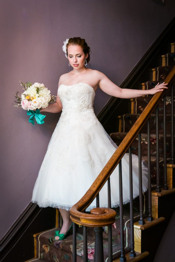 Bride with bouquet coming down stairs at a Round Hill House wedding