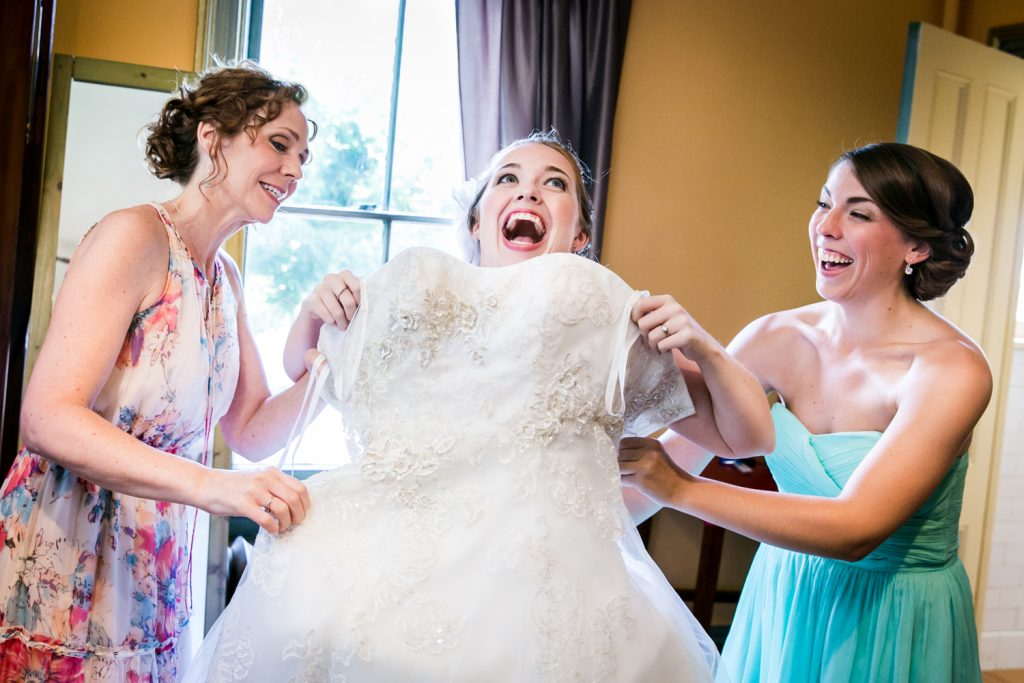 Two women pulling wedding dress on bride at a Round Hill House wedding