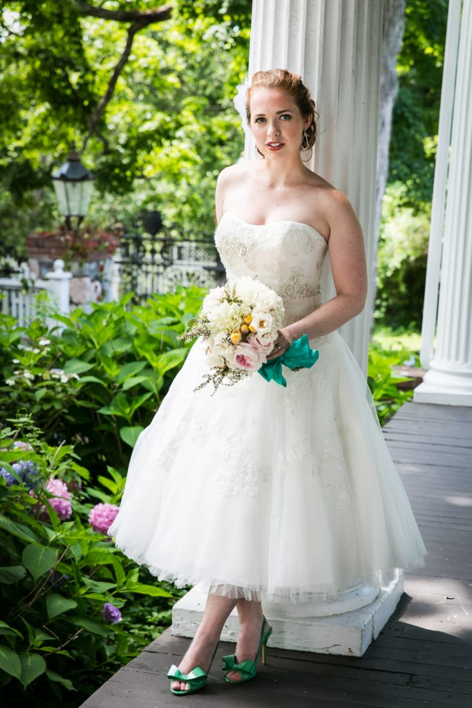 Bride with bouquet standing against column at a Round Hill House wedding