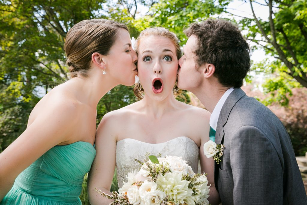 Man and woman kissing bride on both cheeks at a Round Hill House wedding