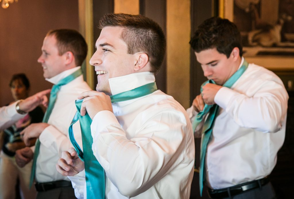Groom and two groomsmen adjusting ties at a Round Hill House wedding