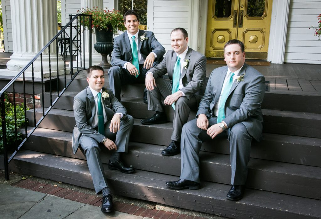 Groom and groomsmen sitting on steps at a Round Hill House wedding