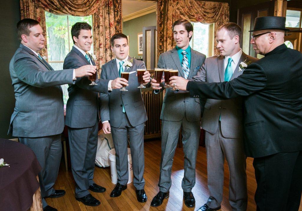 Groom and groomsmen cheering with glasses of beer
