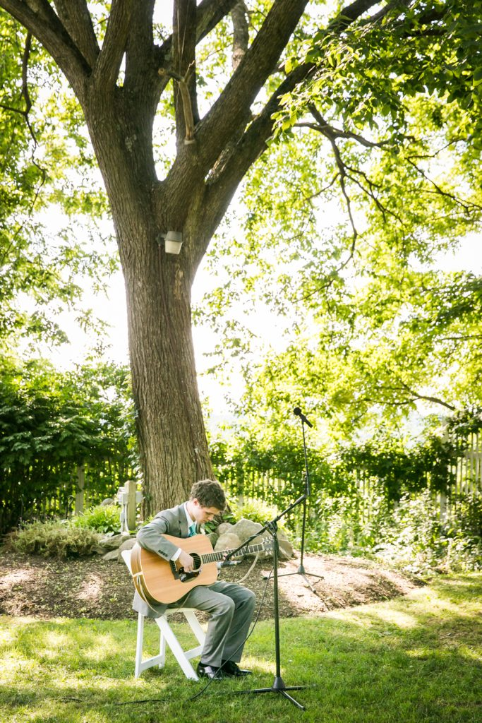 Man sitting in garden playing guitar at ceremony