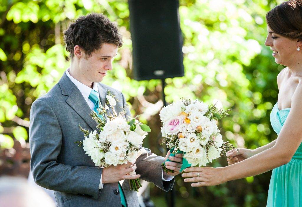 Maid of honor handing bouquets to groomsman at a Round Hill House wedding