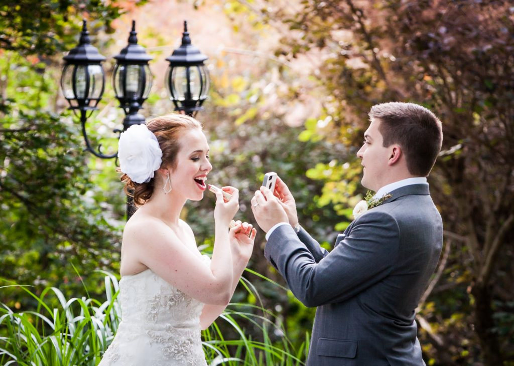 Groom holding mirror for bride who is applying lipstick