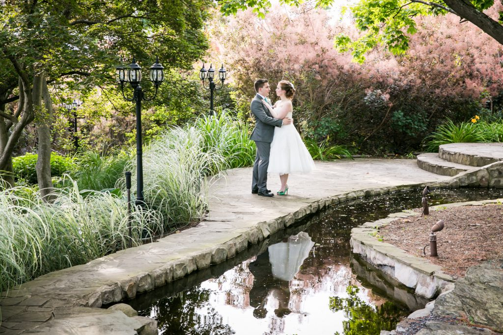 Bride and groom in garden standing by pond at a Round Hill House wedding