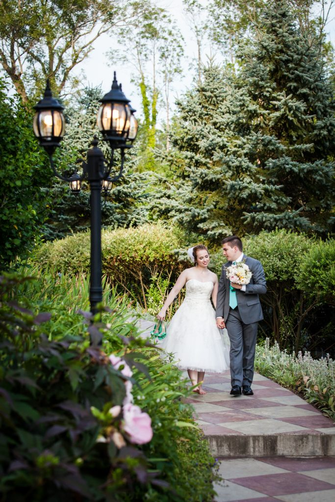 Bride and groom walking down garden pathway at a Round Hill House wedding