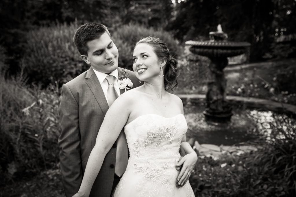 Black and white photo of bride and groom in garden