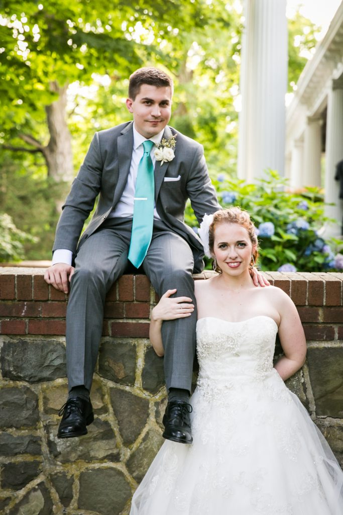 Groom sitting on wall and bride holding leg of groom