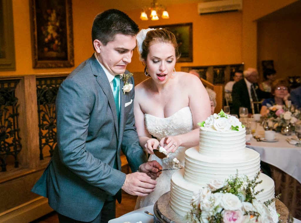 Bride and groom making faces while cutting cake
