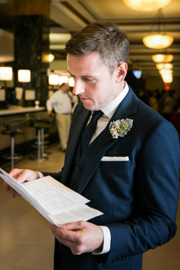 NYC City Hall wedding photos of groom looking at marriage license