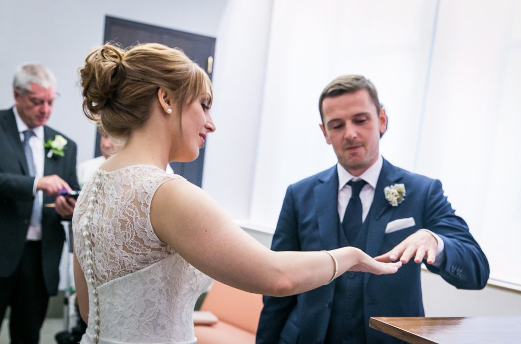 NYC City Hall wedding photos of bride and groom comparing hands
