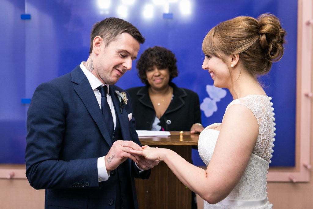 NYC City Hall wedding photos of groom putting ring on bride's finger