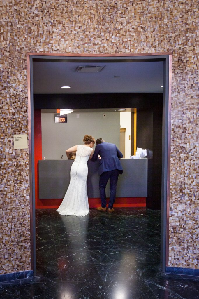 NYC City Hall wedding photos of bride and groom at City Clerks Office desk