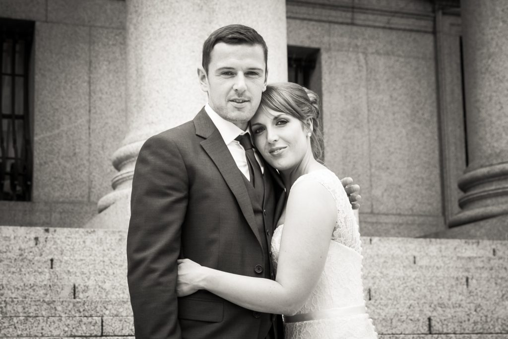 Black and white photo of bride and groom in front of New York County Supreme Court building