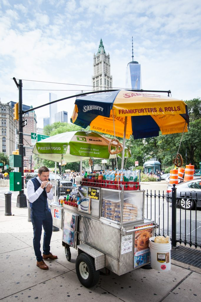 Groom eating in front of hot dog cart