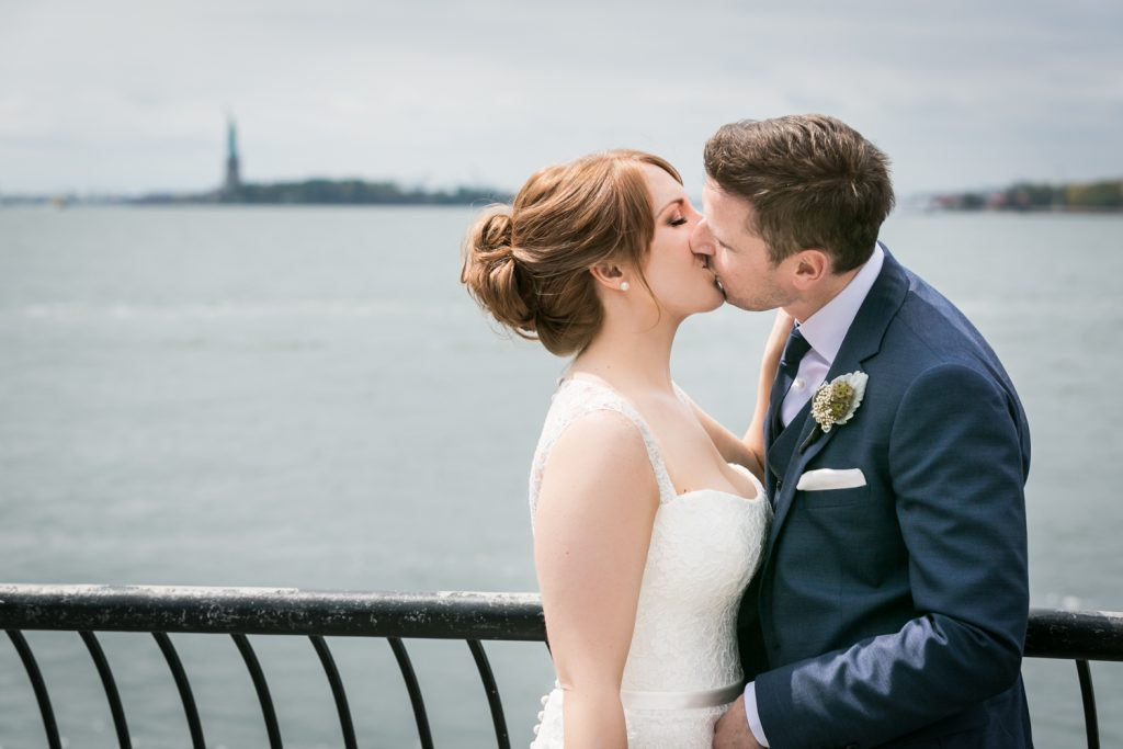 Bride and groom kissing with Statue of Liberty in background