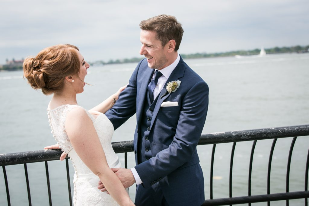 Bride and groom laughing in front of NYC waterfront