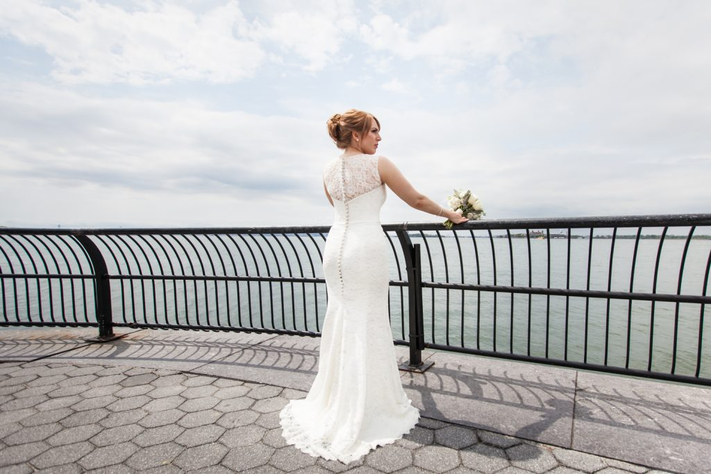 Bride looking over railing at NYC waterfront