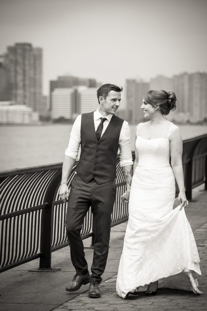 Black and white photo of bride and groom walking along Battery Park