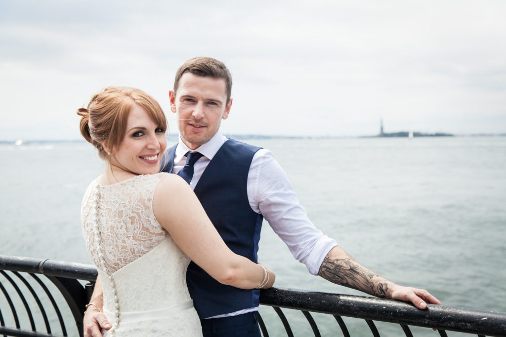 Bride and groom on railing with Statue of Liberty in background