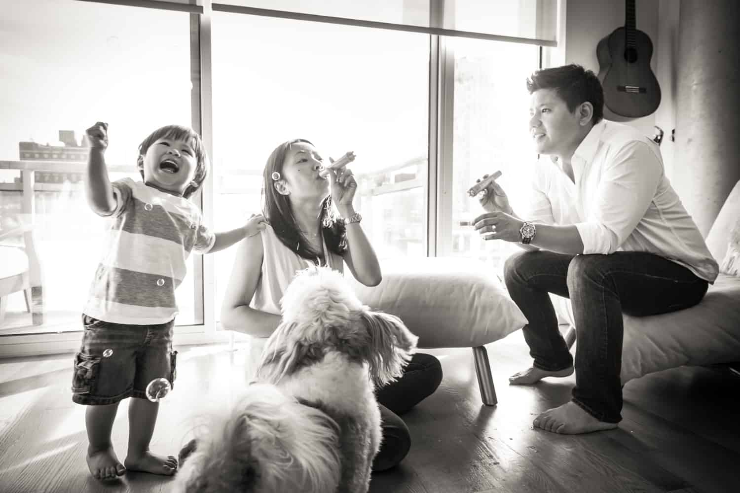 Black and white photo of parents and child blowing bubbles