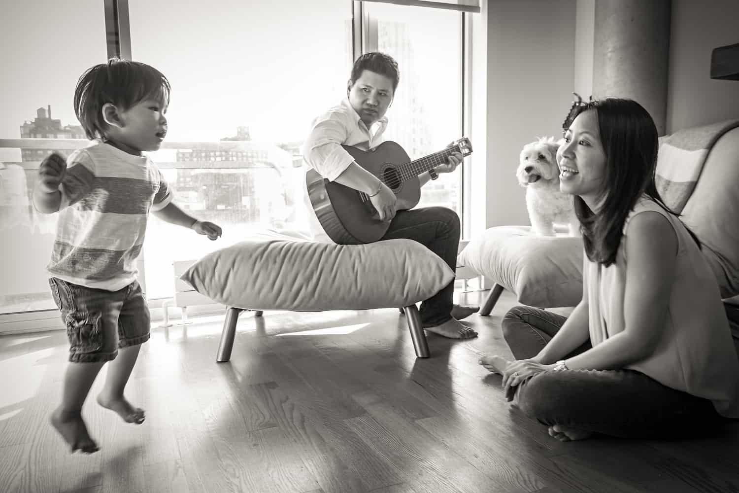 Black and white photo of parents and child playing a guitar