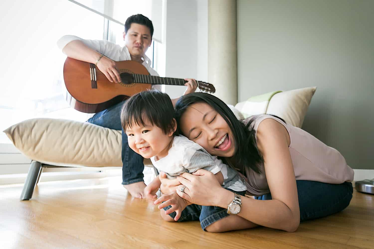 Manhattan family portrait of parents and child playing guitar