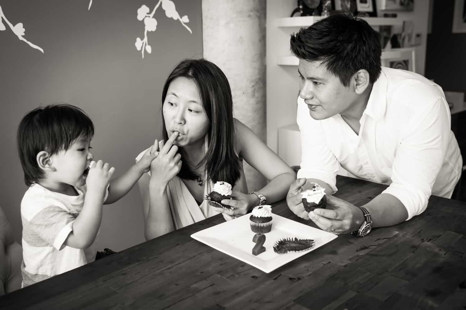 Black and white photo of parents and child eating cupcakes