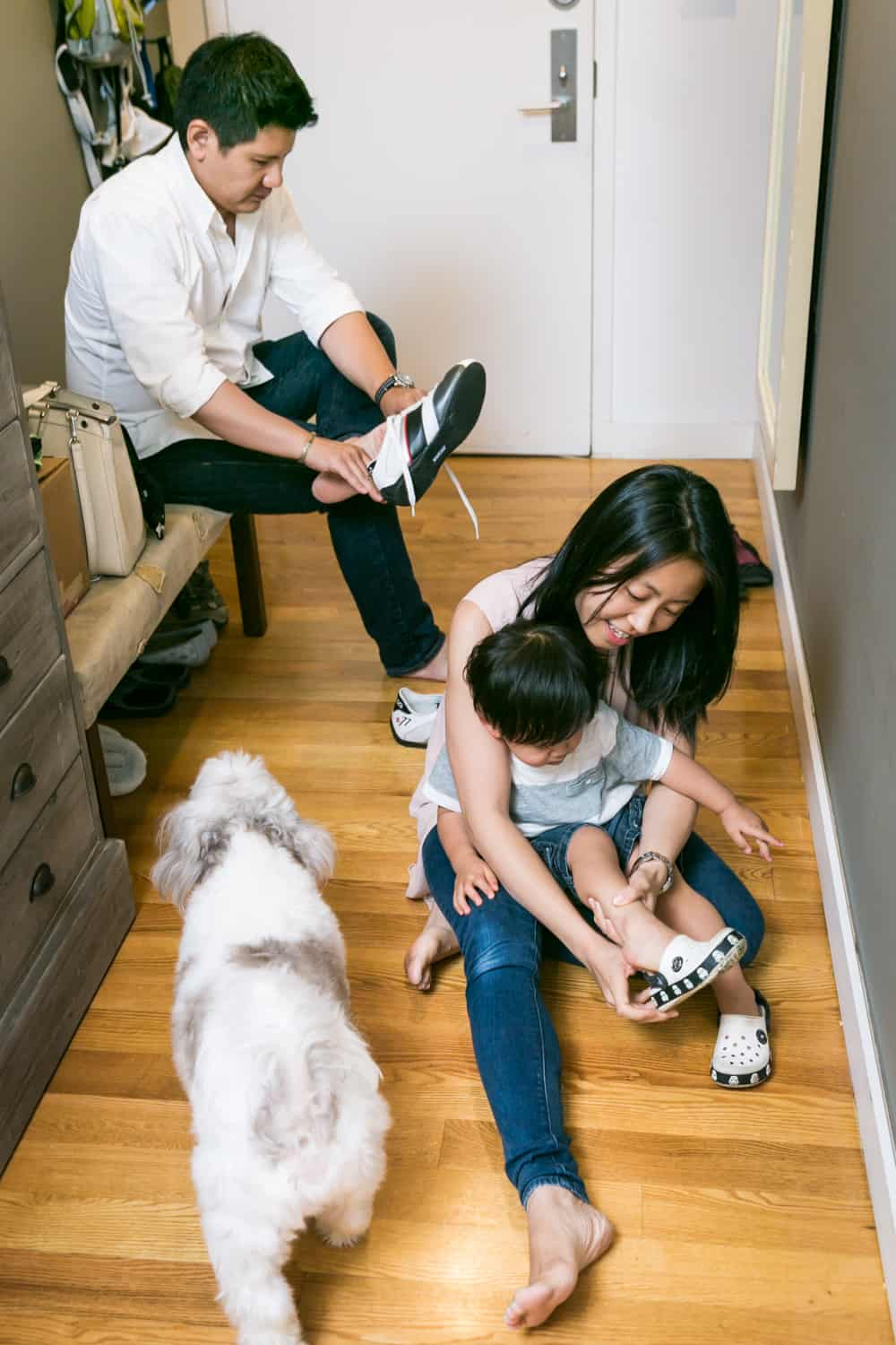 Asian American family putting on shoes in hallway