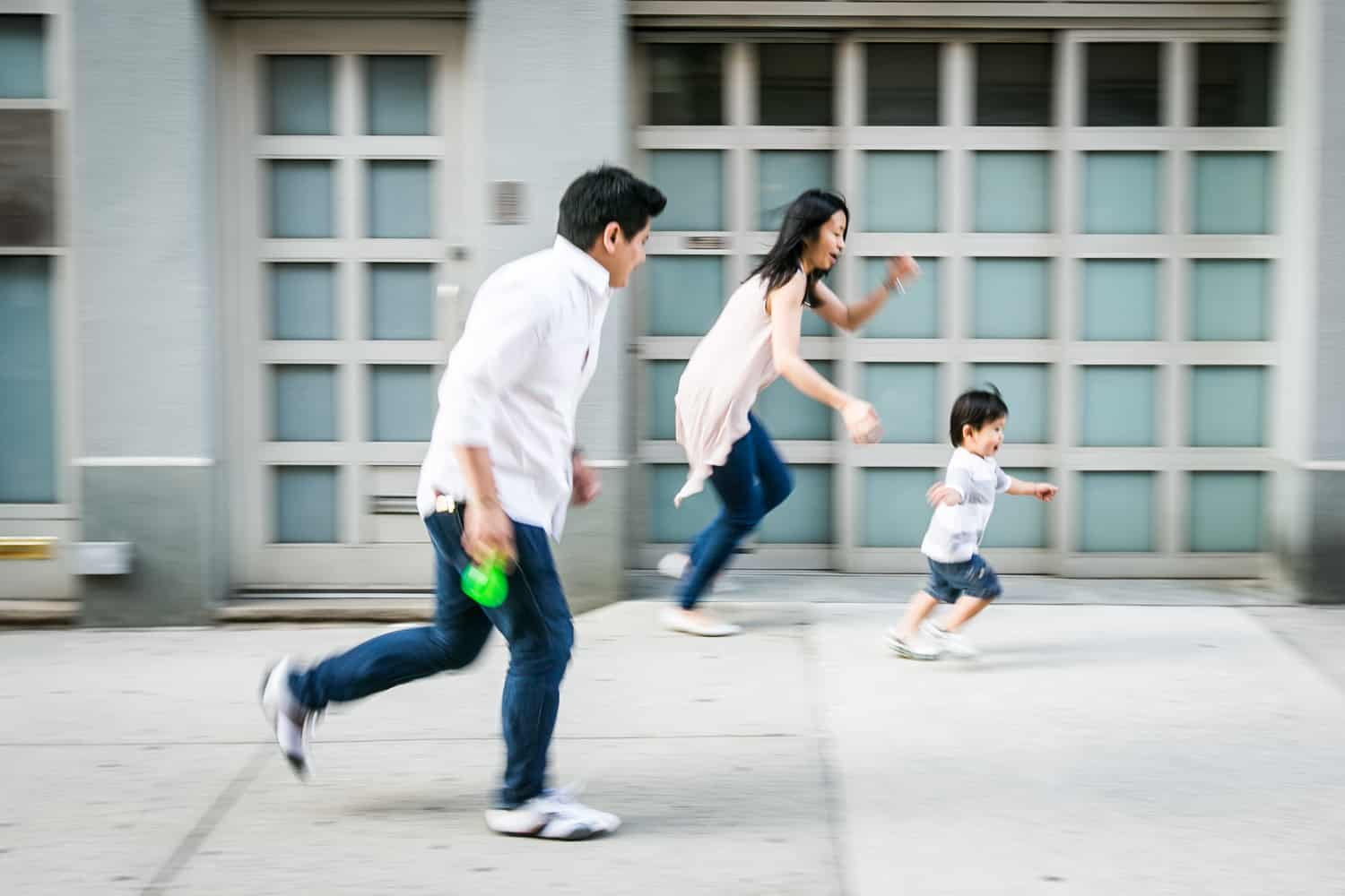 Parents running after little boy on Manhattan sidewalk