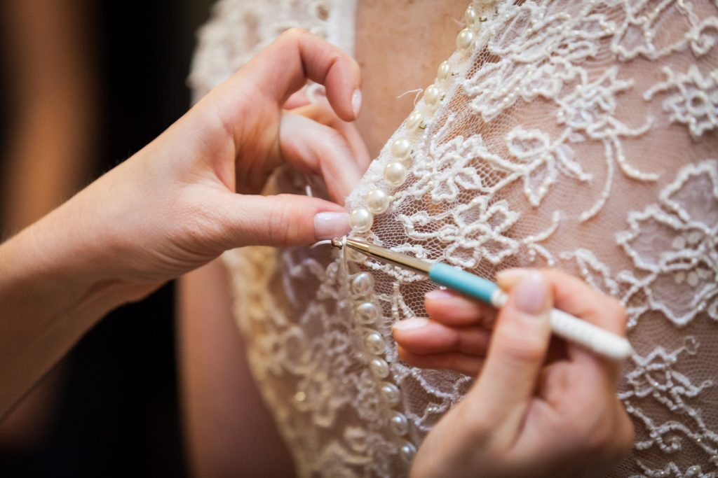 Close up on hands buttoning buttons of lace wedding dress with crochet needle