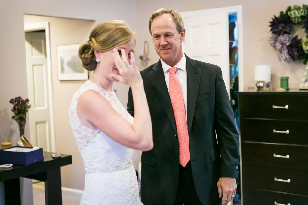 Bride wiping tears from her eye after first look with father