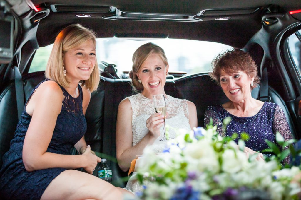 Bride and two women in back of limo with glass of champagne