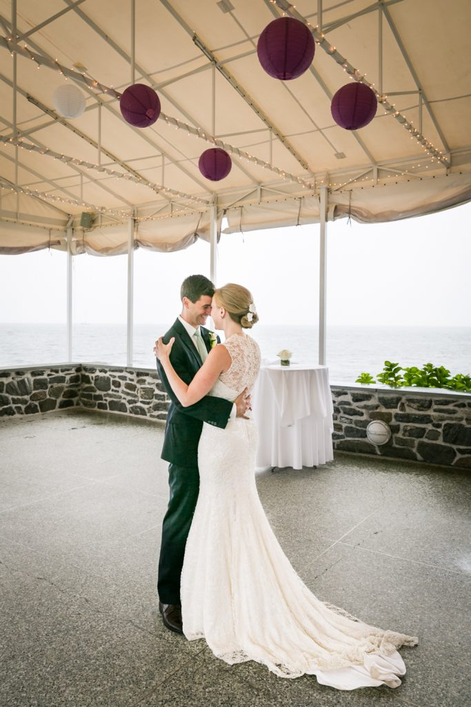 Bride and groom under tent hugging at an American Yacht Club wedding