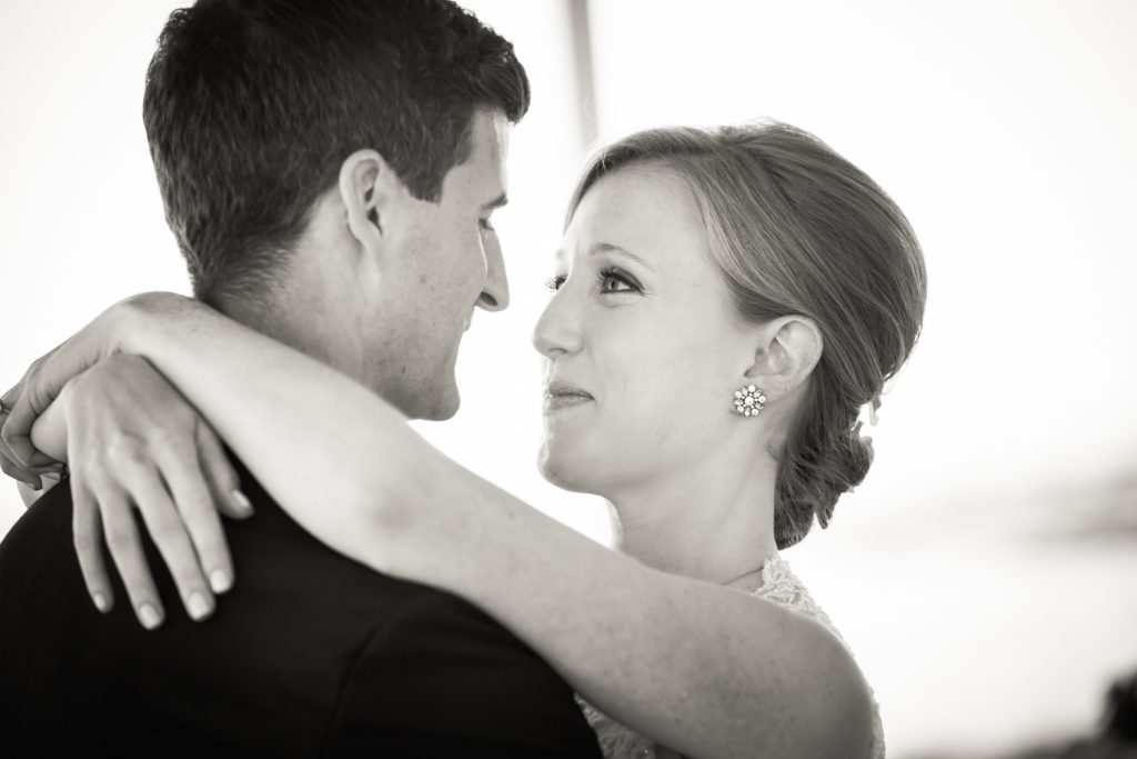 Black and white portrait of bride and groom hugging at an American Yacht Club wedding