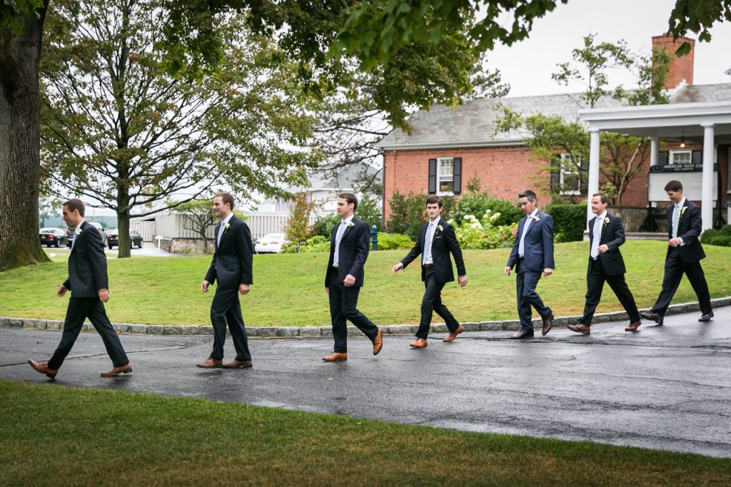 Groom and groomsmen walking in line to ceremony at an American Yacht Club wedding