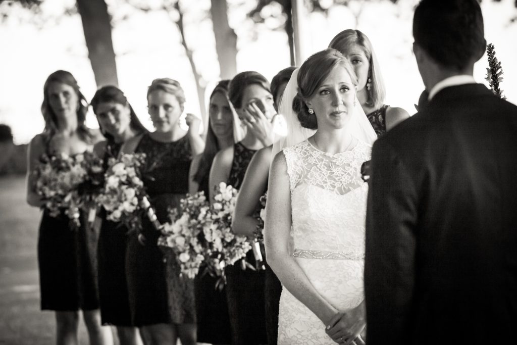 Black and white photo of bride watching groom during ceremony at an American Yacht Club wedding