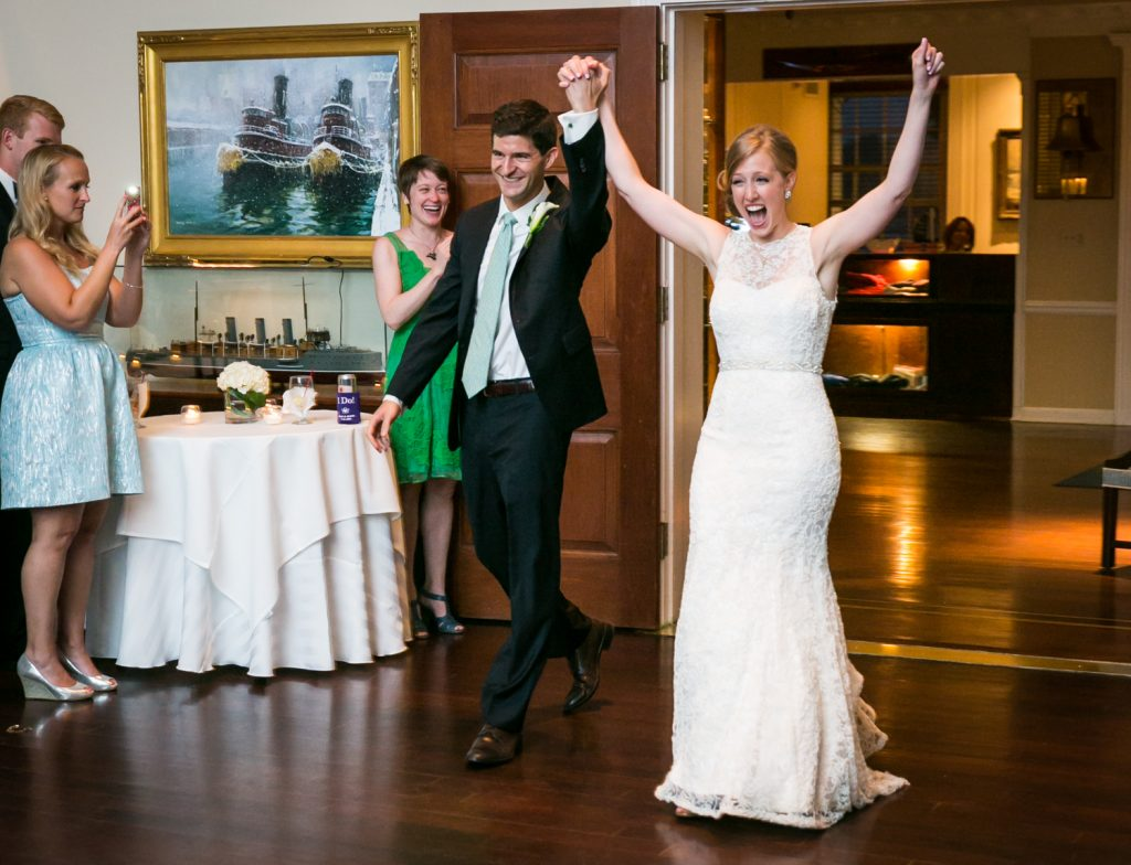 Bride and groom entering reception with arms up at an American Yacht Club wedding