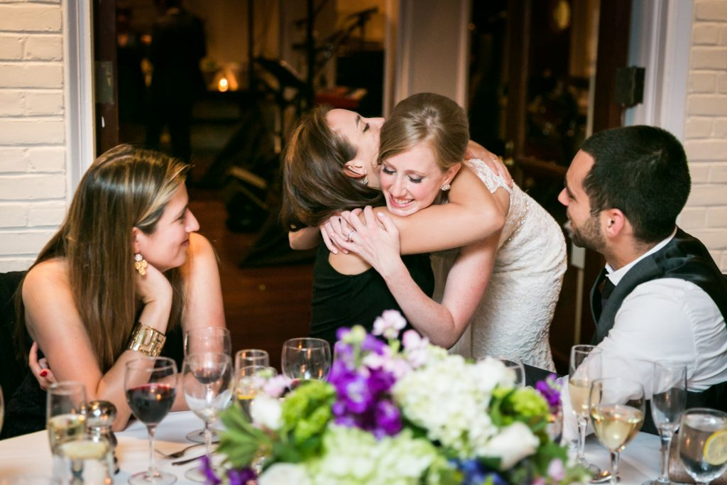 Bride hugging guest at table during reception