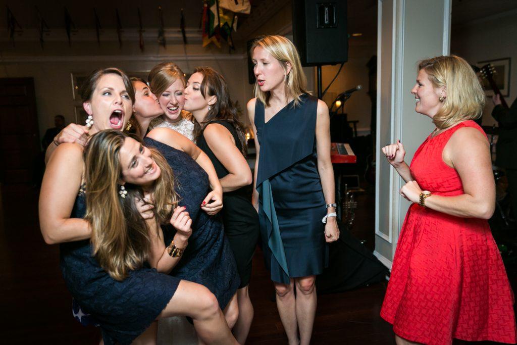 Bride being kissed on both cheeks in crowd of girlfriends