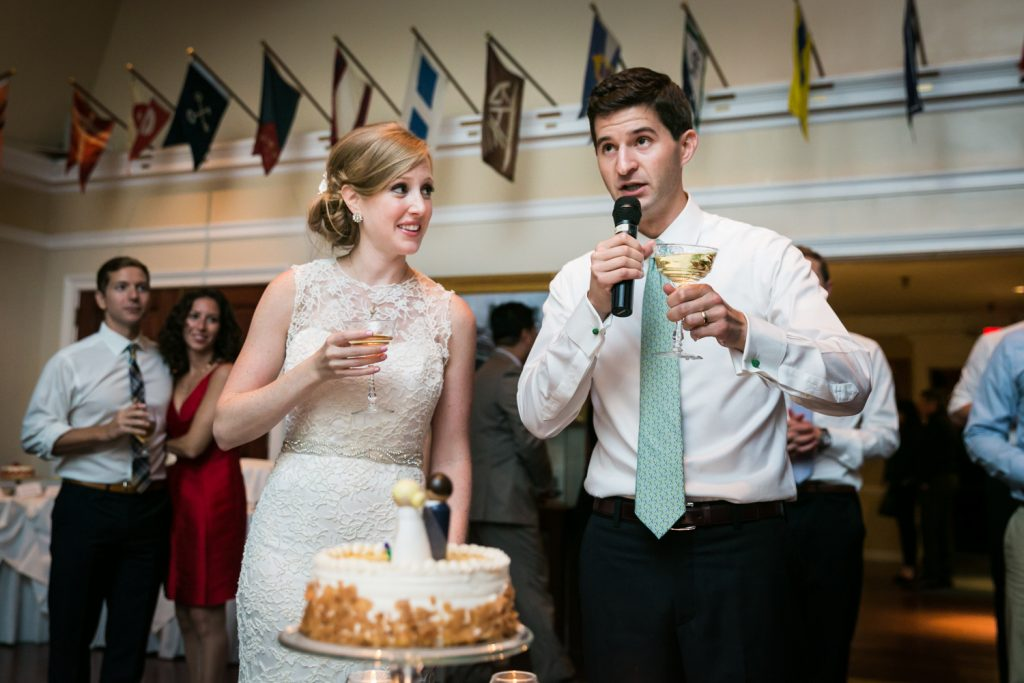 Groom giving speech next to bride holding champagne glass