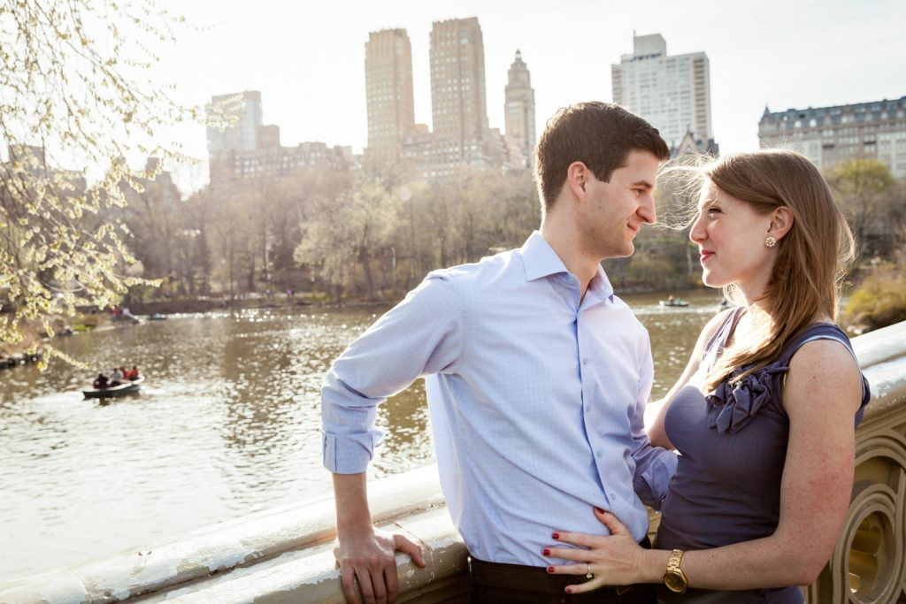 Man and woman looking at each other across from Central Park lake during a Central Park engagement session