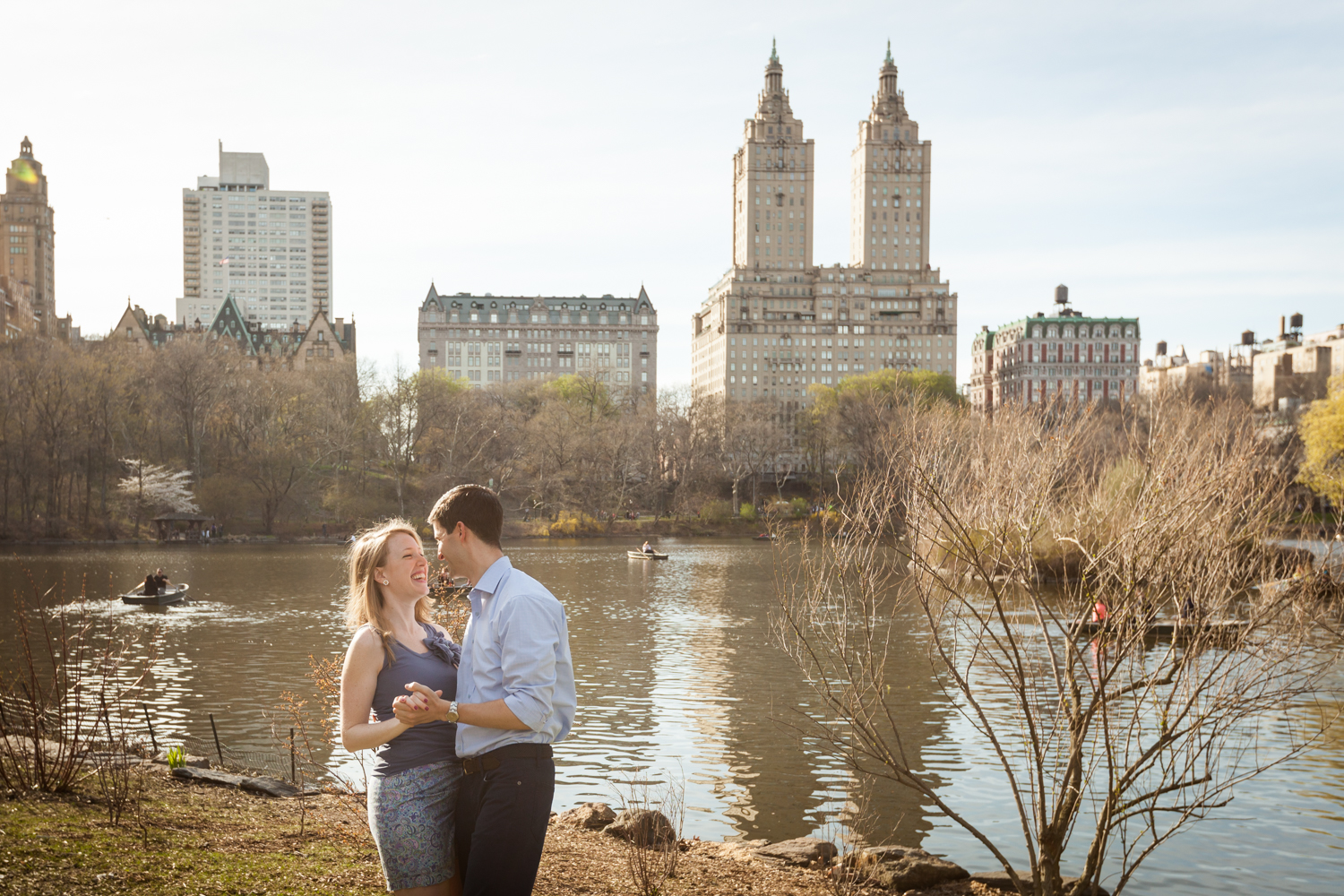 Man and woman dancing across from Central Park lake during a Central Park engagement session