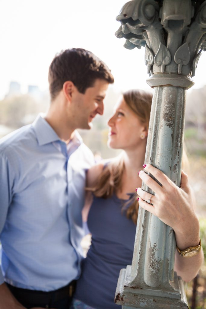 Woman's hand with engagement ring on column with couple out of focus in background