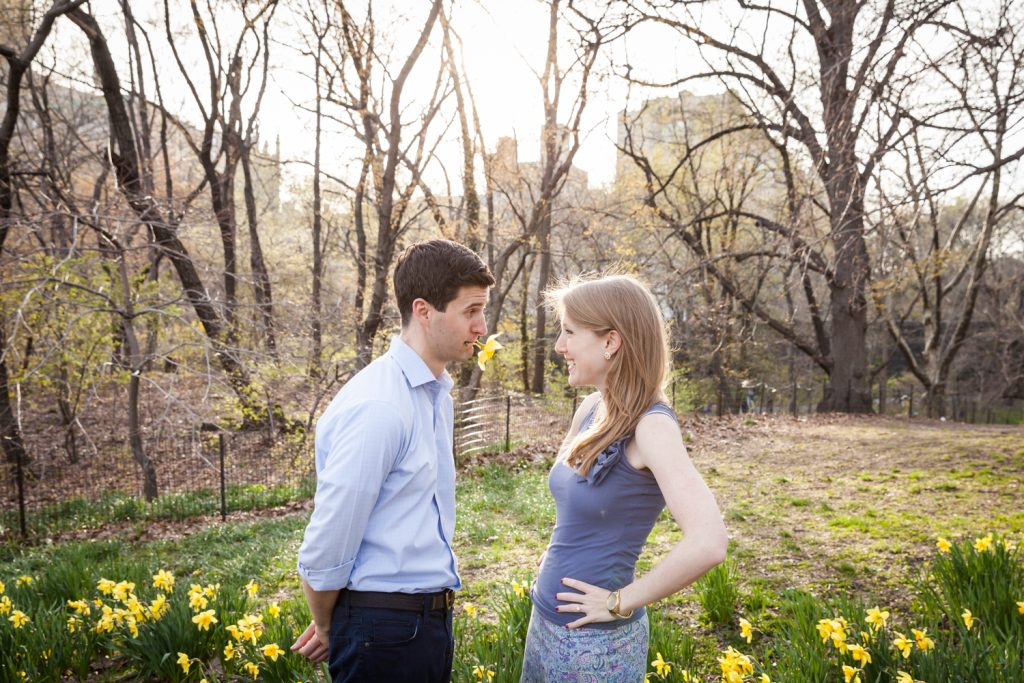 Man with daffodil in mouth next to woman during a Central Park engagement session
