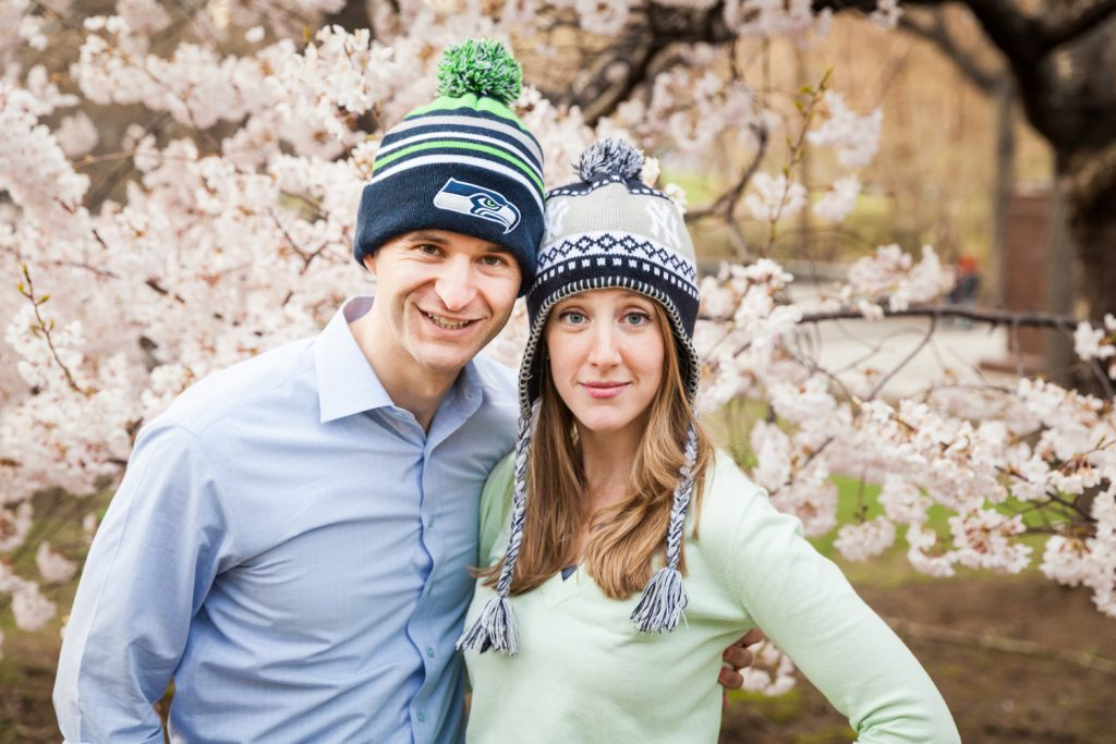 Couple wearing knit caps  in front of cherry blossom trees in Central Park