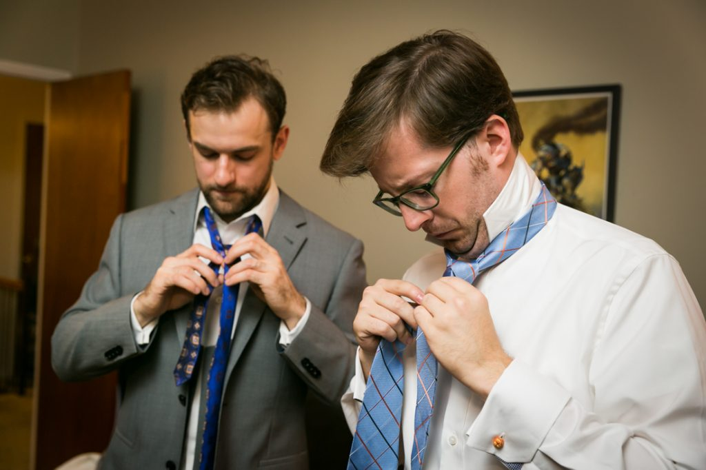 Groom and groomsmen fixing ties before wedding